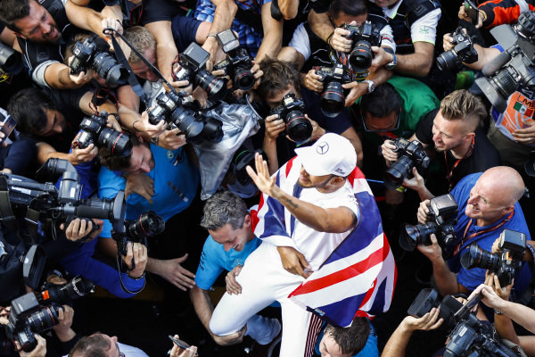 Lewis Hamilton, Mercedes AMG F1, with Union flag draped across his shoulders, celebrates with his team and the photographers after securing a 5th world drivers championship title