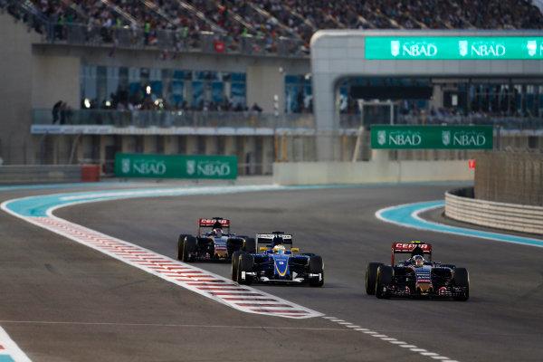 Yas Marina Circuit, Abu Dhabi, United Arab Emirates. Sunday 29 November 2015. Carlos Sainz Jr, Toro Rosso STR10 Renault, leads Marcus Ericsson, Sauber C34 Ferrari, and Max Verstappen, Toro Rosso STR10 Renault. World Copyright: Sam Bloxham/LAT Photographic ref: Digital Image _SBL8753