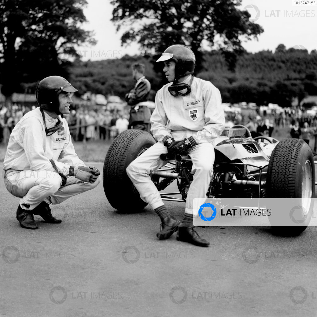 Spa-Francorchamps, Belgium. 12-14 June 1964. Jim Clark (Lotus 25-Climax) talks to Dan Gurney (Brabham BT7-Climax). Both had just run out of fuel but Clark had already finished in 1st position. World Copyright: LAT Photographic Ref: 24999B b&w