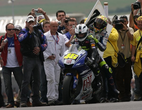 2008 MotoGP Championship - RaceLe Mans, France. 18th May, 2008.Valentino Rossi Fiat Yamaha Team emerges from his Fan Club scrum on the back of his bike riding pillion to Angel Nieto who's race record of 90 wins he has just equalled.World Copyright: Martin Heath / LAT Photographic
