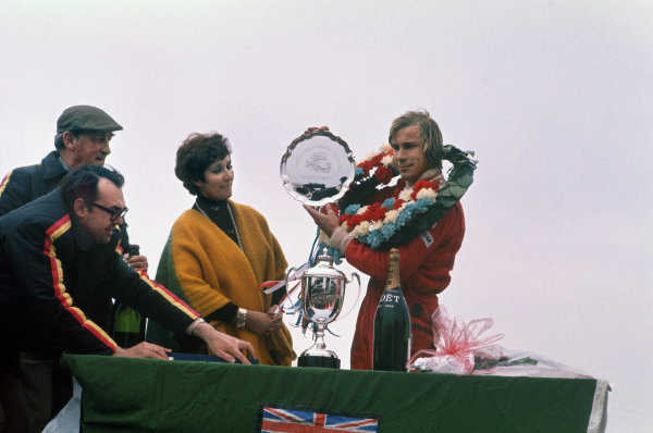 Silverstone, Great Britain. 11th April 1976. James Hunt (McLaren M23-Cosworth), 1st position, on the podium with Betty Hill, wife of Graham Hill, portrait.  World Copyright: LAT Photographic.  Ref:  76 INT 08.
