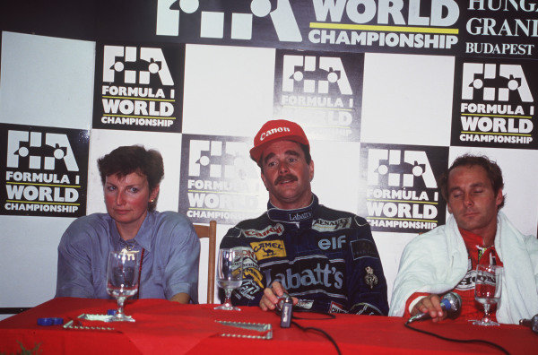 Nigel Mansell, his wife Roseanne, and Gerhard Berger talk to the media.