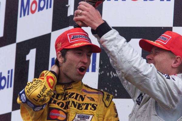 1999 French Grand Prix.Magny-Cours, France.25-27 June 1999. Heinz-Harald Frentzen (Jordan Mugen Honda) celebrates his 1st position on the podium, whilst Mika Hakkinen (McLaren Mercedes) 2nd position pours champagne over him.World Copyright - Lawrence/LAT Photographic