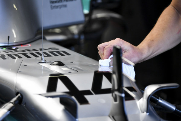 Car of Lewis Hamilton, Mercedes AMG F1 being cleaned by a mechanic