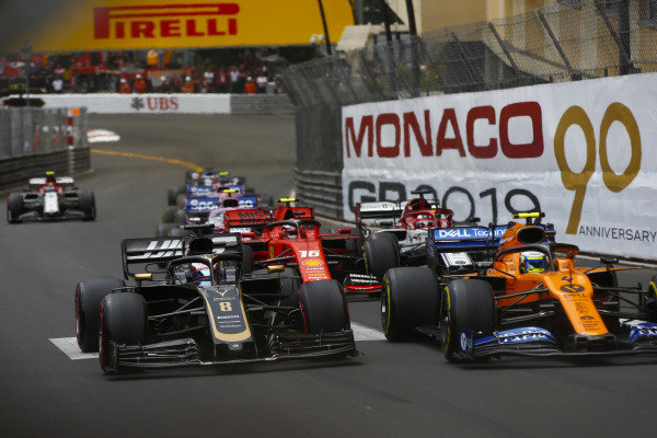 Lando Norris, McLaren MCL34, leads Romain Grosjean, Haas VF-19, Charles Leclerc, Ferrari SF90, Kimi Raikkonen, Alfa Romeo Racing C38, and the remainder of the field at the start