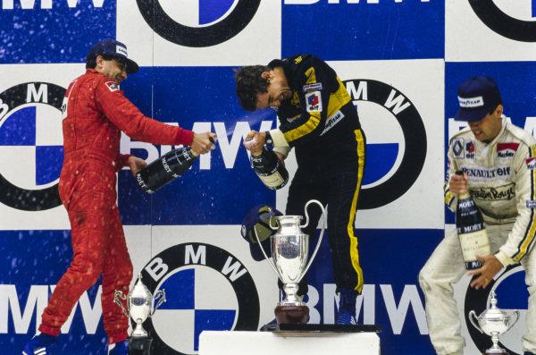 Ayrton Senna, 1st position, celebrates on the podium with Michele Alboreto, 2nd position, and Patrick Tambay, 3rd position.