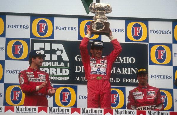 1991 San Marino Grand Prix.Imola, Italy.26-28 April 1991.Ayrton Senna (McLaren MP4/6 Honda) celebrates 1st position with Gerhard Berger (McLaren MP4/6 Honda) 2nd position and J J. Lehto (Dallara Judd) 3rd position on the podium.Ref-91 SM 38.World Copyright - LAT Photographic