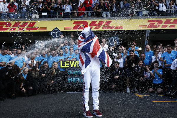 Lewis Hamilton, Mercedes AMG F1, is sprayed with Champagne by his team after securing his fifth world drivers title